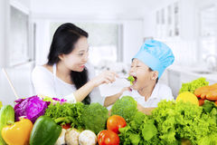 Boy tasting salad in kitchen. Healthy little boy and his mother tasting vegetable salad in the kitchen at home Stock Image