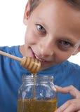Boy tasting some honey. Close up Stock Photo