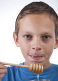 Boy tasting some honey. Close up Royalty Free Stock Photos