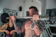 Boy with tattooed body does workout in the gym using weights, girl with kettlebell. stock photo