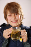 Boy with tea Stock Images
