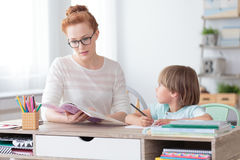 Boy and teacher in classroom stock image