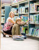 Boy And Teacher Selecting Books From Bookshelf Stock Photo