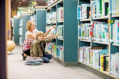 Boy With Teacher Selecting Books From Bookshelf Royalty Free Stock Photos