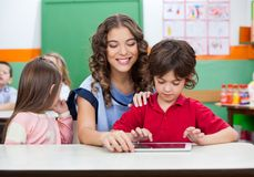 Boy With Teacher Using Digital Tablet Royalty Free Stock Photography