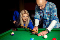 Boy teaches girl how to hit in billiards Royalty Free Stock Image