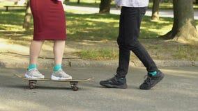 Boy teaching geek girl to ride skateboard, unusual friendship, youth hobbies