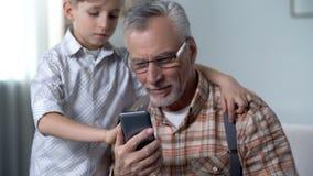 Boy teaching grandpa to use smartphone, digital nation against older generation royalty free stock photo