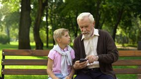 Boy teaching grandpa to use smartphone, new technologies difficult for pensioner