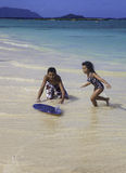 Boy teaching sister to skim board Stock Images