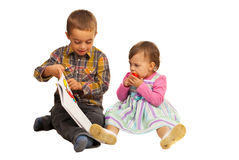Boy teaching toddler girl about book. Preschool boy teaching his little sister and showing book paper isolated on white background Stock Image