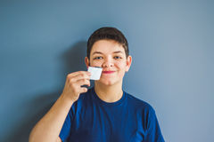 Boy tears off an adhesive tape from a mouth Stock Images