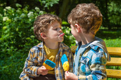 Boy tease with tongue. Three year old identical twins are holding the candy in the colors of the Ukrainian flag. Candy shows the Ukrainian Trident. Children Royalty Free Stock Photo
