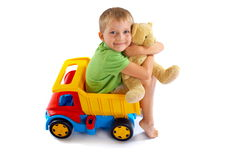 Boy with teddy bear. Cute boy sitting on toy truck and hugging his teddy bear Royalty Free Stock Image