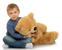 Boy with a Teddy bear. Beautiful little boy sitting on the floor. The boy holds by the neck a large Teddy bear - Isolated on white background Stock Images