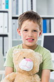 Boy with teddy bear in clinic Stock Images