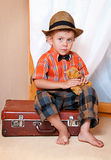 A boy with a teddy bear sitting on a suitcase. Stock Images