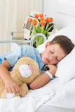 Boy with teddy bear sleeping in hospital Stock Image