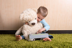 Boy with teddy bear. Boy and teddy bear with tablet computer stock images