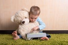 Boy with teddy bear. Boy and teddy bear with tablet computer royalty free stock photos