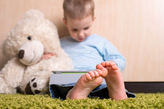 Boy with teddy bear. Boy and teddy bear with tablet computer, barefoot in focus royalty free stock images