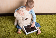 Boy and teddy bear. With tablet computer, Top view stock photography
