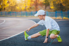 Boy Teen doing sports exercises on a stadium Stock Images
