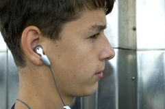 Boy or teen with headphones. Teen listen music on mp3 player or cell-phone royalty free stock photos