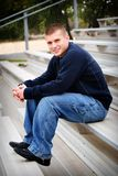 Boy teen model 2. A young man sitting on bleachers Royalty Free Stock Photo