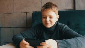 Boy teen playing on black smartphone in a stylish cafe. Boy teen playing on a black smartphone in a stylish cafe stock video
