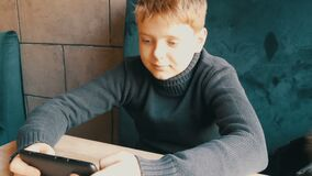 Boy teen playing on black smartphone in a stylish cafe. Boy teen playing on a black smartphone in a stylish cafe stock footage