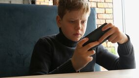 Boy teen playing a game on black smartphone. Boy teen playing a game on a black smartphone stock video