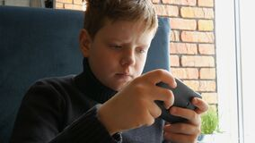 Boy teen playing a game on black smartphone. Boy teen playing a game on a black smartphone stock footage