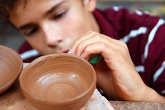 Boy teen potter clay bowl working. In pottery workshop traditional arts Royalty Free Stock Photos