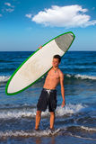 Boy teen surfer holding surfboard in the beach. Boy handsome teen surfer holding surfboard in the blue beach Royalty Free Stock Images