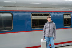 Boy teen with a travel bag near train Royalty Free Stock Photo