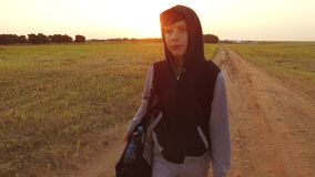 Boy teen traveling. Boy teenage tramp walking along the road in a hood with backpacks a sad traveler video steadicam. Boy teen traveling. Boy teenage tramp royalty free stock photo