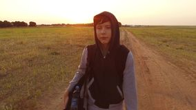Boy teen traveling. Boy teenage tramp walking along the road in a hood with backpacks a sad traveler video steadicam. Boy teen traveling. Boy teenage tramp royalty free stock images
