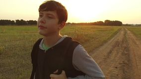Boy teen traveling. Boy teenage tramp walking along the road in hood with backpacks a sad traveler video steadicam shot. Boy teen traveling. Boy teenage tramp royalty free stock images