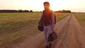 Boy teen traveling. Boy teenage tramp walking along the road in a hood with backpacks a sad traveler. Boy teen traveling. Boy teenage tramp walking along the stock image