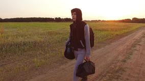 Boy teen traveling. Boy teenage tramp walking along the road in a hood with backpacks a sad traveler. Boy teen traveling. Boy teenage tramp walking along the stock photo