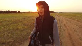 Boy teen traveling. Boy teenage tramp walking along the road in hood with backpacks a sad traveler video steadicam shot. Boy teen traveling. Boy teenage tramp Royalty Free Stock Photography