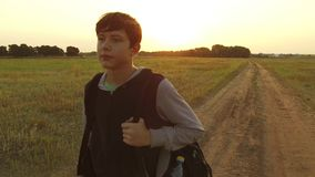 Boy teen traveling. Boy teenage tramp walking along the road in hood with backpacks a sad traveler video steadicam shot. Boy teen traveling. Boy teenage tramp Royalty Free Stock Image