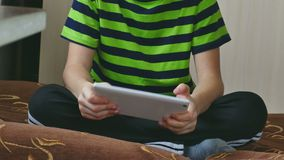 Boy teenage playing on tablet sitting on couch stock video