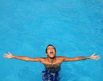 Boy teenage relaxed open arms blue swimming pool Royalty Free Stock Photos