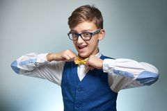 Boy teenager with braces in glasses. Wearing a shirt with a bow tie. Boy with glasses and a shirt straightens a bow tie, on the teeth of dental braces stock image
