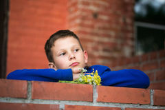 Boy teenager on a brick wall background. Royalty Free Stock Image