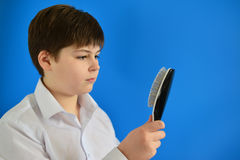 Boy teenager with comb in his hand Royalty Free Stock Photo