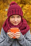 Boy teenager with a cup of tea coffee in a voluminous large cozy scarf and cap of burgundy color Royalty Free Stock Photography