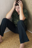 Boy teenager with depression sitting in the corner of room Royalty Free Stock Photo